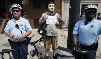 A Black Lives Matters protestor stands beside police officers during a protest march in downtown Philadelphia on Monday during the first day of the Democratic National Convention. (Associated Press)