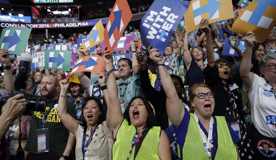 Carrie Pugh, left, Katrina Mendiola and Mayors Wegmann cheer as Hillary Clinton officially becomes the first woman to be the presidential nominee of a major U.S. political party during the second day session of the Democratic National Convention in Philadelphia, Tuesday, July 26, 2016. (AP Photo/John Locher)