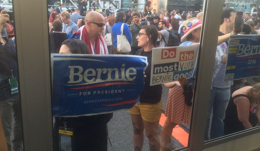 Sanders delegates storm the media tents outside the Democratic National Convention, holding pro-Sanders signs and saying they'll never accept Hillary Clinton as the party's presidential nominee. (Ben Wolfgang/The Washington Times)
