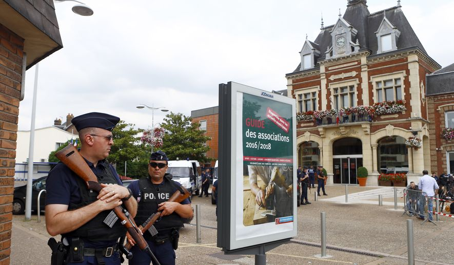 French police officers stand guard in front of the Saint-Etienne-du-Rouvray's city hall, Normandy, France, after an attack on a church that left a priest dead, Tuesday, July 26, 2016. Two attackers invaded a church Tuesday during morning Mass near the Normandy city of Rouen, killing an 84-year-old priest by slitting his throat and taking hostages before being shot and killed by police, French officials said. (AP Photo/Francois Mori)