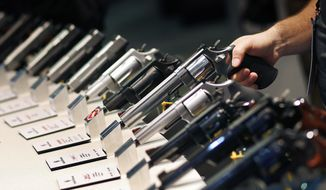 FILE - In this Jan. 19, 2016 file photo, handguns are displayed at the Smith & Wesson booth at the Shooting, Hunting and Outdoor Trade Show in Las Vegas. Nearly two-thirds of Americans expressed support for stricter gun laws, according to an Associated Press-GfK poll released Saturday, July 23, 2016. A majority of poll respondents oppose banning handguns. (AP Photo/John Locher, File)