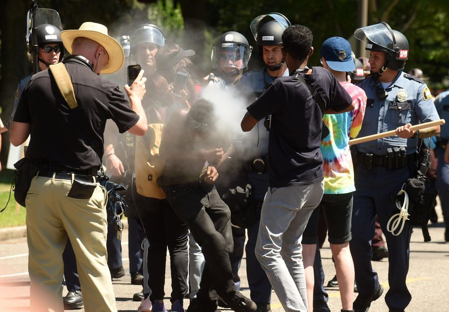 16-year old Tayvion Owens is sprayed with a substance by St. Paul police officers as they and protesters face off on Summit Ave., a block from the Governor's residence, in St. Paul, Minn. on Tuesday, July 26, 2016. Police have arrested an unknown number of protesters in front of the governor's mansion on St. Paul's Summit Avenue. Demonstrators have been camping outside the governor's residence since early July 7, a day after the shooting of Philando Castile, who was killed by a St. Anthony police officer during a traffic stop. (Scott Takushi/Pioneer Press via AP)