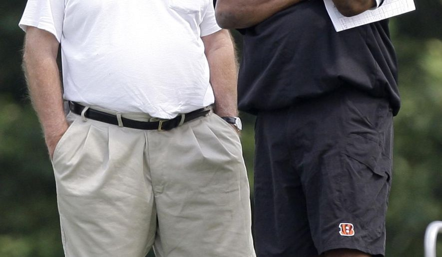 FILE - In this Aug. 1, 2010, file photo, Cincinnati Bengals president Mike Brown, left, talks with head coach Marvin Lewis during practice at the NFL football team's training camp in Georgetown, Ky. Mike Brown is being very patient with his one-and-done Bengals, keeping the team intact _ including coach Marvin Lewis _ even though it has lost its opening-round playoff game an NFL record five straight years. (AP Photo/Al Behrman, File)