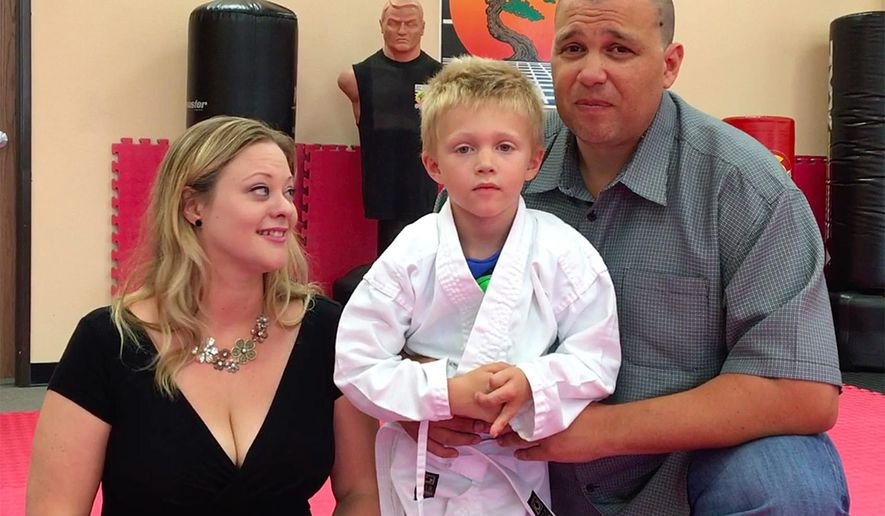 Liam Brenes, 4, with his parents, Amanda McFarland, and Frank Brenes at United Karate studio in Mission Viejo, Calif., on Tuesday, July 26, 2016.  Brenes had his custom prosthetic leg stolen at Crystal Cove State Park on Sunday, but was able to earn his white belt by using his older prosthetic leg. When word got out, people started offering replacements or donations. An online campaign has raised more than $15,000. (Nick Koon/The Orange County Register via AP)