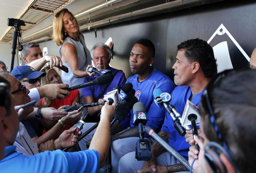 CORRECTS TO RELIEVER- Chicago Cubs reliever Aroldis Chapman, center, listens to a question as he meets reporters before a baseball game between the Chicago White Sox and Cubs Tuesday, July 26, 2016, in Chicago. (AP Photo/Charles Rex Arbogast)