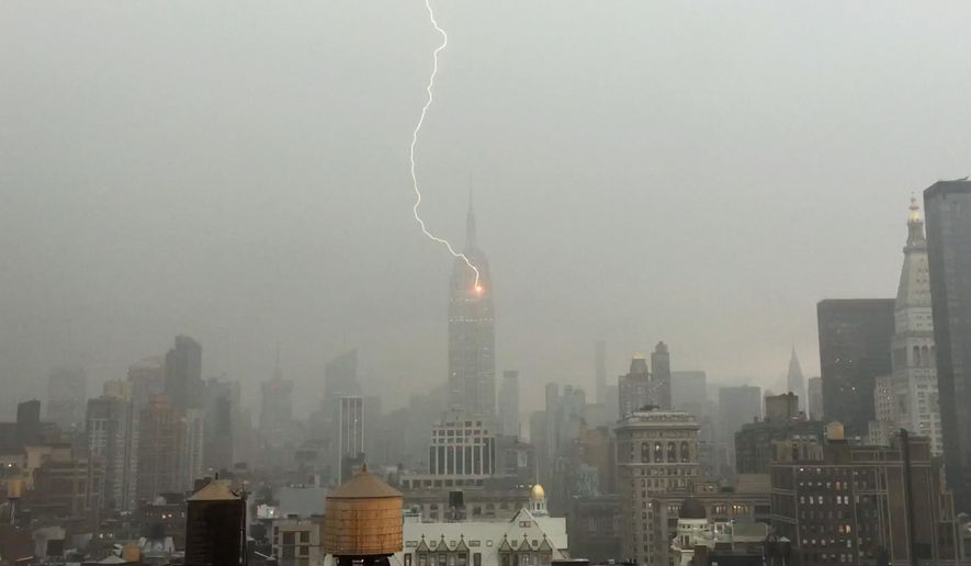In this Monday, July 25, 2016 frame from video provided by Henrik Moltke, lightning strikes the Empire State Building during a storm in New York. Moltke said he saw the storm approaching from his office window and captured the strike by balancing his phone against the glass. (Henrik Moltke via AP)