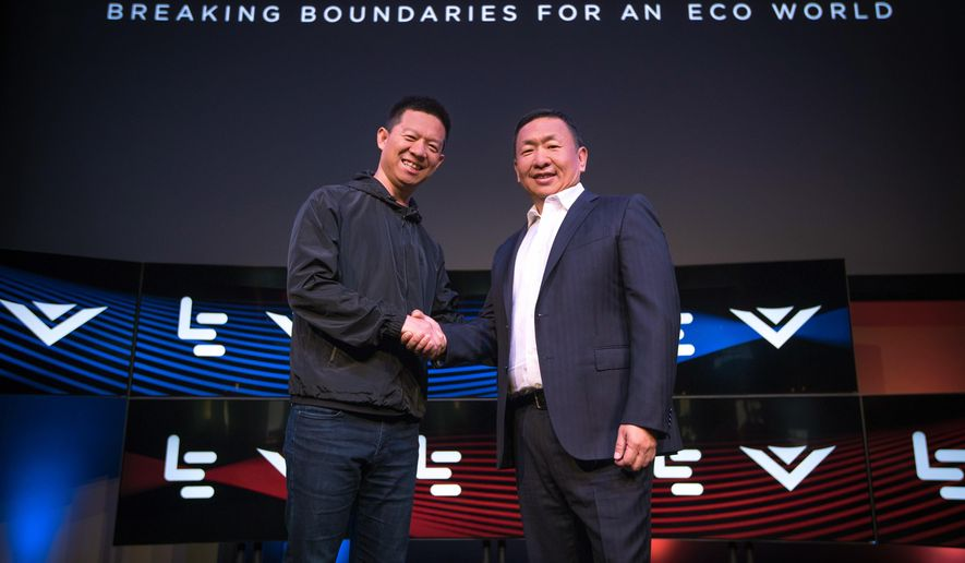 In this photo provided by LeEco, LeEco CEO Jia Yueting, left, and Vizio CEO William Wang shake hands at a news conference where it was announced that LeEco had acquired Vizio for $2 billion, Tuesday, July 26, 2016, in Los Angeles. (Jeff Lewis/LeEco via AP)