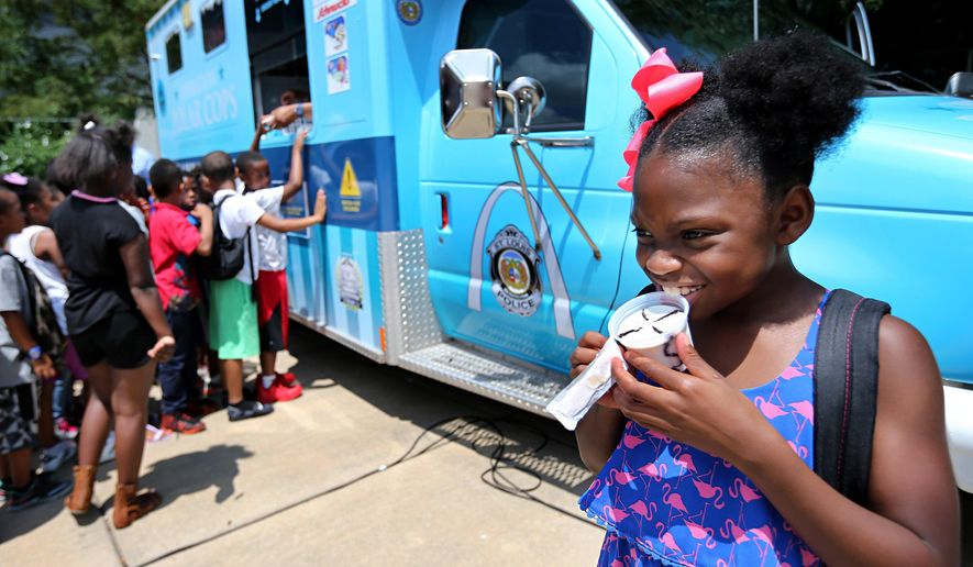 Amara Boyd, 7, opens up her ice cream after a press conference where police announced the start of Operation Polar Cops at the Boys & Girls Club on N. Grand Boulevard on Tuesday, July 26, 2016 in St. Louis. The program puts police officers in an ice cream truck handing out free treats to kids to help create positive experiences between the police and the community. (David Carson/St. Louis Post-Dispatch via AP)