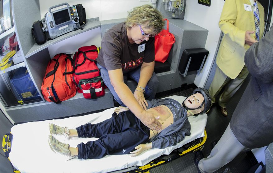 Polly Olson, an EMS instructor from Chappell, Neb., looks at simulated injuries on a mannequin, in a mobile training unit parked outside the University of Nebraska Medical Center in Omaha, Neb., Tuesday, July 26, 2016. A $5.5 million grant from the Leona and Harry Helmsley foundation will pay for four specialized training trucks to be stationed across the state for three years. The trucks have high-tech simulators in the back that can be used to help train people on advanced techniques, such as opening a patient's airway after a car accident. About 80 percent of Nebraska's emergency responders are volunteers, and it can be hard for them to get certified in such advanced techniques. (AP Photo/Nati Harnik)