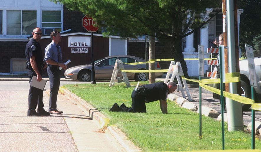 Law enforcement officers check for any evidence possibly left behind at the scene of a traffic stop where shots were fired in Antigo, Wis., Tuesday, July 26, 2016. Authorities said an armed suspect has been killed by police in the township of Pine River after a standoff and pursuit that began after shots were fired at an officer in Antigo. (Fred Berner/Antigo Daily Journal via AP)