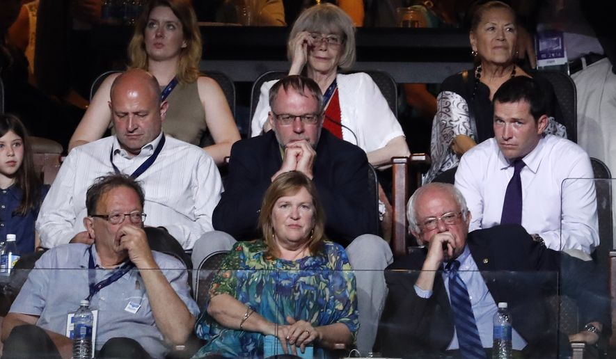 Former Democratic presidential candidate Bernie Sanders sits next to wife Jane as Democratic vice presidential candidate, Sen. Tim Kaine, D-Va., takes the stage during the third day of the Democratic National Convention in Philadelphia , Wednesday, July 27, 2016. (AP Photo/Paul Sancya)