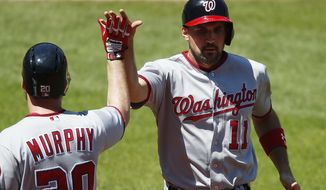 Washington Nationals' Ryan Zimmerman, right, celebrates with Daniel Murphy, left, after scoring on a hit by Trea Turner during the first inning of a baseball game Wednesday, July 27, 2016, in Cleveland. (AP Photo/Ron Schwane)