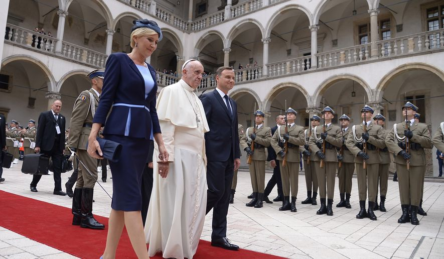 Pope Francis, center, flanked by Polish President Andrzej Duda, right, and his wife, Agata Kornhauser-Duda,  arrives for an official welcoming ceremony at the royal Wawel Castle in Krakow, Poland, Wednesday, July 27, 2016. The world is at war, but it is not a war of religions, Pope Francis said Wednesday as he traveled to Poland on his first visit to Central and Eastern Europe in the shadow of the slaying of a priest in France. (Filippo Monteforte/Pool Photo via AP)