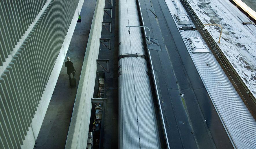 A man walks along a parking garage above Amtrak trains waiting to depart Union Station in Washington on Nov. 25, 2015. (Associated Press)