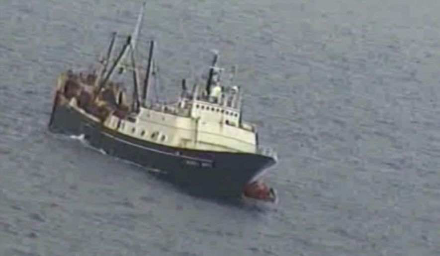 In this Tuesday, July 26, 2016 frame from video provided by the U.S. Coast Guard, crew from a sinking fishing boat, left, board life rafts off Alaska's Aleutian Islands in the Bering Sea. When the Alaska Juris started taking on water Tuesday, crew members donned survival suits and got into rafts. (U.S. Coast Guard via AP)