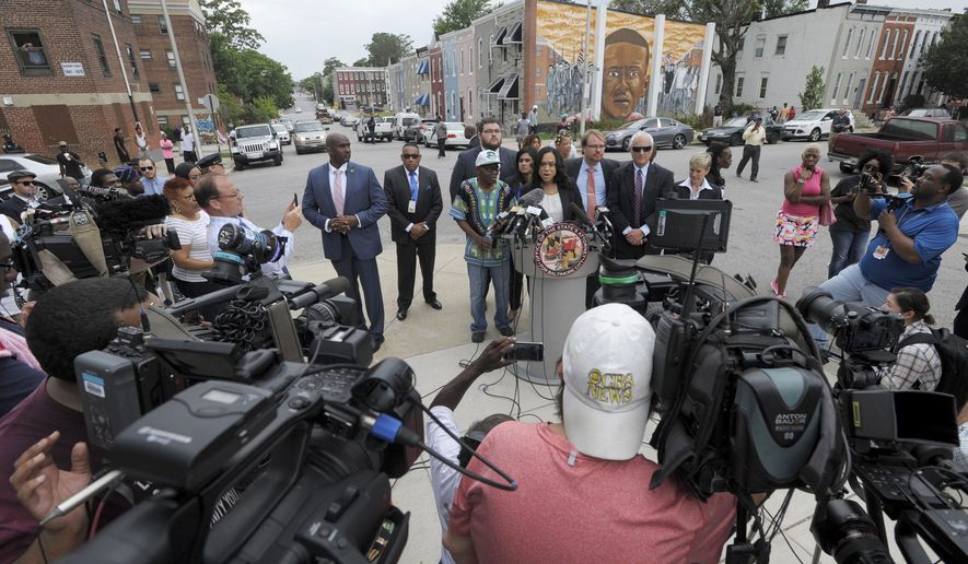 Baltimore State's Attorney Marilyn Mosby, at podium, holds a news conference near the site where Freddie Gray, depicted in mural in background, was arrested after her office dropped the remaining charges against three Baltimore police officers awaiting trial in Gray's death, in Baltimore, Wednesday, July 27, 2016. The decision by prosecutors comes after a judge had already acquitted three of the six officers charged in the case. At left is Gray's father, Richard Shipley. (AP Photo/Steve Ruark)