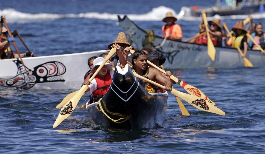A canoe from the Puyallup Tribe is paddled toward a landing during an annual journey Wednesday, July 27, 2016, in Seattle. Dozens of tribal canoes were arriving at Alki Beach in Seattle as part of an annual Native American celebration. Members of the Muckleshoot Tribe greeted the boats Wednesday afternoon as part of the 2016 Paddle to Nisqually. (AP Photo/Elaine Thompson)