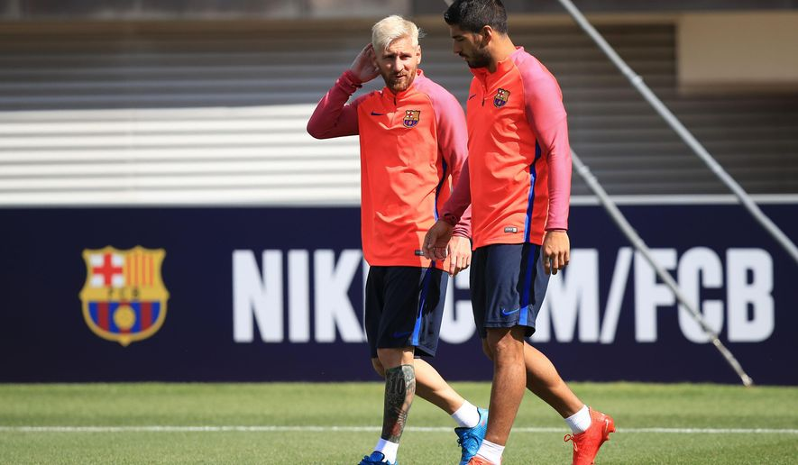Barcelona's Lionel Messi, left, speaks with teammate Luis Suarez during a training session at St George's Park, Burton, England, Wednesday, July 27, 2016. (Mike Egerton/PA via AP)