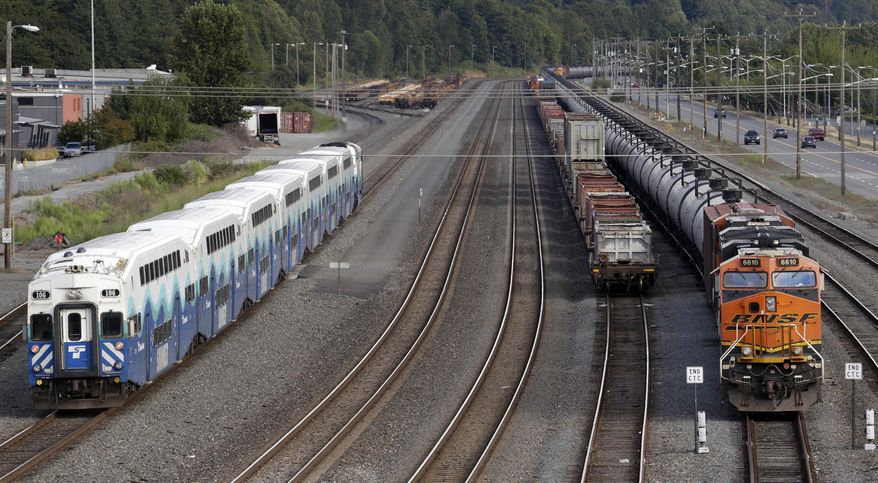 FILE - In this July 27, 2015, file photo, a passenger commuter train, left, passes one of two mile-long oil trains parked adjacent to the King County Airport in Seattle. As oil trains began rolling through its downtown a few years ago, Spokane, Wash, was among the first cities to pass a resolution calling for tougher state and federal safety regulations. But when an oil train derailed in a fiery crash in Oregon last month, after earlier rumbling through the Eastern Washington city, some city leaders didn't want to wait for the federal government to act. The Spokane City Council decided 6-0 to ask voters whether the city should fine companies that ship crude oil or coal by rail through downtown, Wednesday, July 27, 2016. (AP Photo/Elaine Thompson, File)