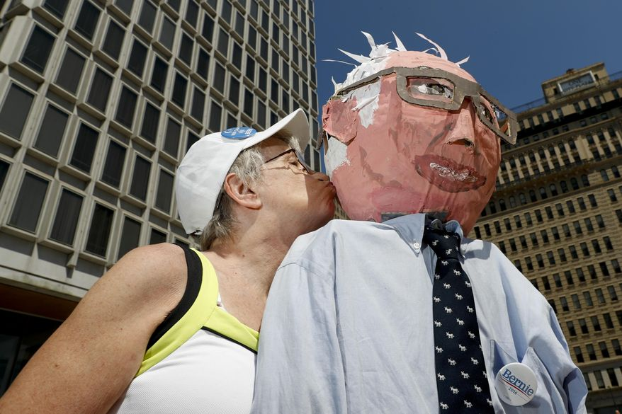 Sue Kirby poses for a picture with a larger-than-life Bernie Sanders, papier-mache head in Philadelphia, Wednesday, July 27, 2016, during the third day of the Democratic National Convention. Kirby, 65, built the doll about a year ago for Sanders rallies near home in Salem, Mass. She learned from a lifetime of activism that having a prop is a good way to get public (and media) attention. (AP Photo/Alex Brandon)