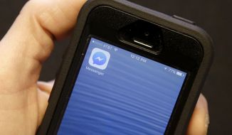 An Associated Press reporter holds a mobile phone showing the Facebook Messenger app icon in San Francisco, Wednesday, July 27, 2016. (AP Photo/Jeff Chiu)