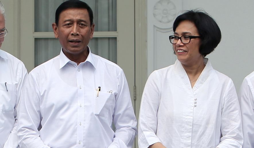 """Indonesia's new Finance Minister Sri Mulyani Indrawati, right, and Coordinating Minister for Legal, Security and Politics Wiranto prepare for a group photo during the announcement of the new cabinet ministers at Merdeka Palace in Jakarta, Indonesia, Wednesday, July 27, 2016. Indonesian President Joko """"Jokowi"""" Widodo announced a new Cabinet line-up on Wednesday that returns a reformist to the Finance Ministry and puts a former head of the military in charge of security. (AP Photo/Tatan Syuflana)"""