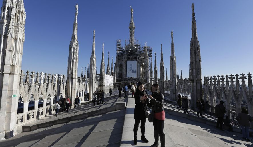 FILE - This file photo taken on Sunday, Jan. 25, 2015, tourists relax on the roof atop the Duomo gothic cathedral, in Milan Italy. Italian police say an American tourist spent a night locked on the spectacular rooftop of Milan's Gothic-inspired Duomo cathedral after being overlooked by security. (AP Photo/Luca Bruno, file)