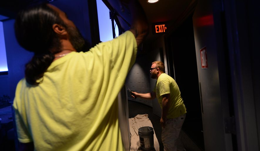 In this Tuesday, July 26, 2016 photo, Max Perry, left, and Ryan White, right, paint at Abrams Planetarium at Michigan State University in East Lansing, Mich. Michigan State University's planetarium has closed its 2015-2016 season for building renovations. The renovations at Abrams Planetarium will include new interactive touch screens, an electronic display previewing upcoming shows, fresh coats of paint and a handicap-accessible ramp, the Lansing State Journal reported. (Julia Nagy /Lansing State Journal via AP)