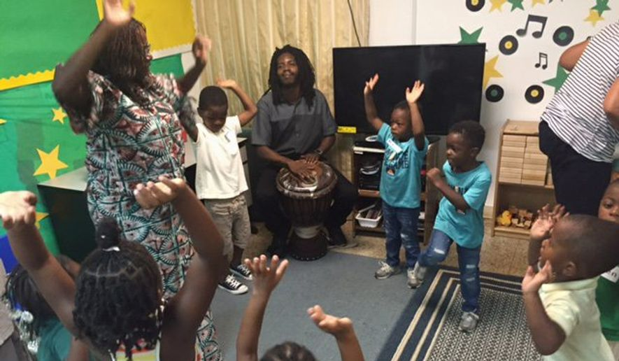 Children form a drum circle to learn African drumming, music and dance from teaching artists Sylvia Soumah and Abdou Muhammad for Inner City-Inner Child, an arts outreach program. (Aubri Juhasz/The Washington Times)