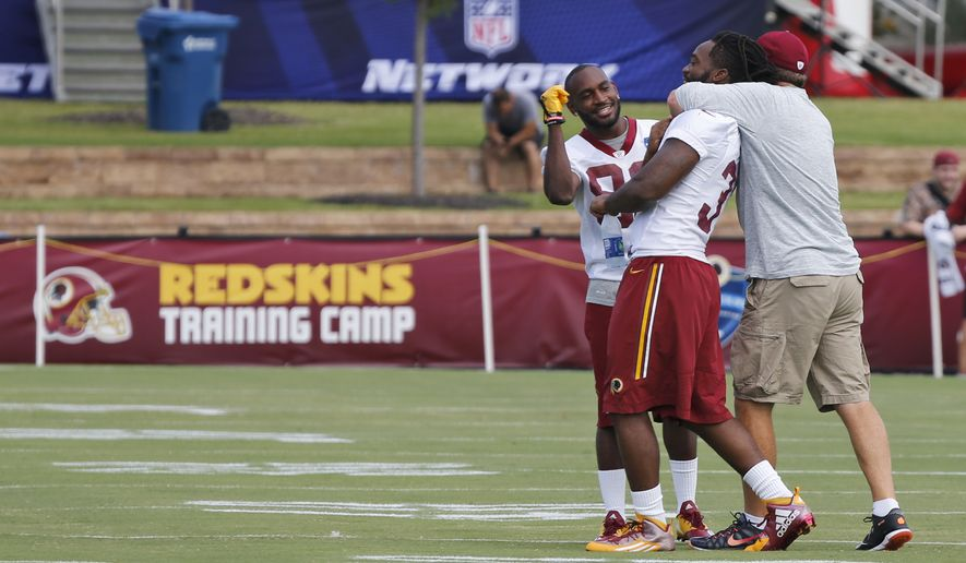 Washington Redskins head football coach Jay Gruden, right, puts a choke hold on running back Matt Jones as wide receiver Jamison Crowder, left, looks on at the start of the NFL football teams training camp in Richmond, Va., Thursday, July 28, 2016. (AP Photo/Steve Helber)