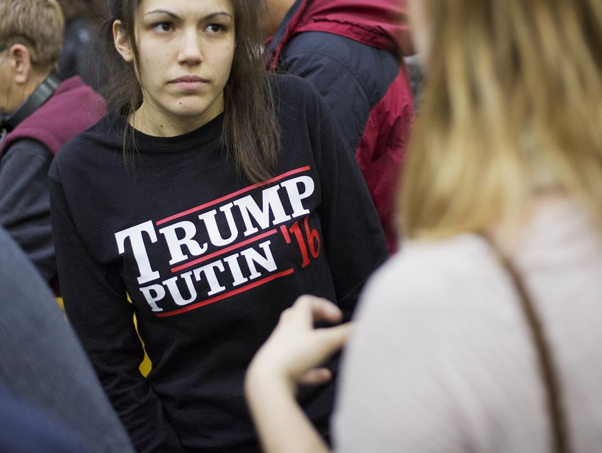 In this Sunday, Feb. 7, 2016, file photo, a woman wears a shirt reading 'Trump Putin '16' while waiting for Republican presidential candidate Donald Trump to speak at a campaign event at Plymouth State University in Plymouth, N.H. (AP Photo/David Goldman, File)