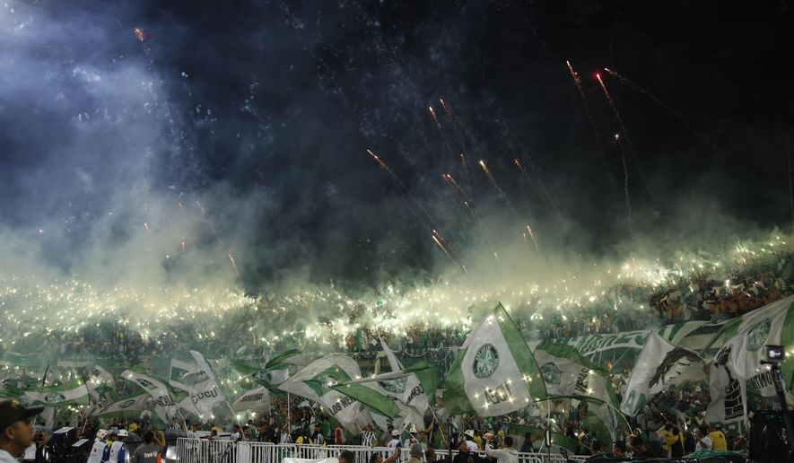 Fans of Colombia's Atletico Nacional cheer for their team as fireworks light up the sky before Copa Libertadores final match against Ecuador's Independiente del Valle in Medellin, Colombia, Wednesday, July 27, 2016. (AP Photo/Fernando Vergara)