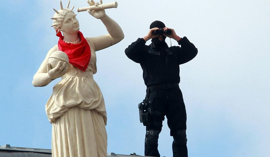 """In this photo taken on Wednesday, July 27, 2016, a French police officers watches the festivities through binoculars on the roof of the town hall, during the opening night of the Bayonne festival, or """"Fetes de Bayonne"""", in Bayonne, southwestern France.  Bayonne, the cultural capital of the French Basque country, hosts the yearly traditional Bayonne festival from July 27-31, and is expected to attract about one million people this year from all over France, Spain, and other European countries. (AP Photo/Bob Edme)"""