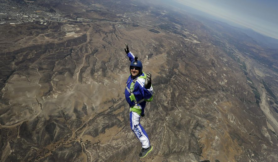 In this Monday, July 25, 2016 photo, skydiver Luke Aikins smiles as he jumps from a helicopter during his training in Simi Valley, Calif. After months of training, this elite skydiver says he's ready to leave his chute in the plane when he bails out 25,000 feet above Simi Valley on Saturday. That's right, no parachute, no wingsuit and no fellow skydiver with an extra one to hand him in mid-air. (AP Photo/Jae C. Hong)