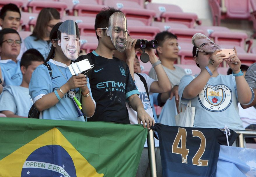 Fans of British soccer club Manchester City watch the players train before a match in Shenzhen in south China's Guangdong province Wednesday, July 27, 2016. The club will face Borussia Dortmund in a friendly match Thursday. (Chinatopix Via AP)