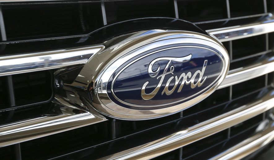 FILE - In this Thursday, Nov. 19, 2015, photo, the Ford blue oval badge is in the grill of a 2015 Ford F-150 XLT on display in the showroom at Butler County Ford in Butler, Pa. Ford reports financial results Thursday, July 28, 2016. (AP Photo/Keith Srakocic, File)
