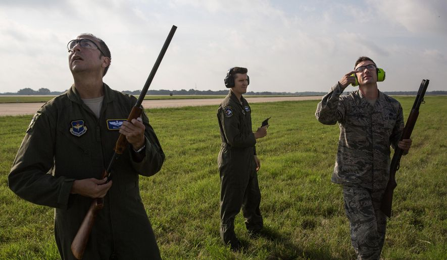 In this June 15, 2016 photo, from left, Maj. Will Rose, Maj. Chris Bernardo and Master Sgt. John Reagan stand ready to fire non-lethal ammo at birds to deter them from entering the flight path at Randolph Air Force Base, in Universal City, Texas. (Ray Whitehouse/The San Antonio Express-News via AP)