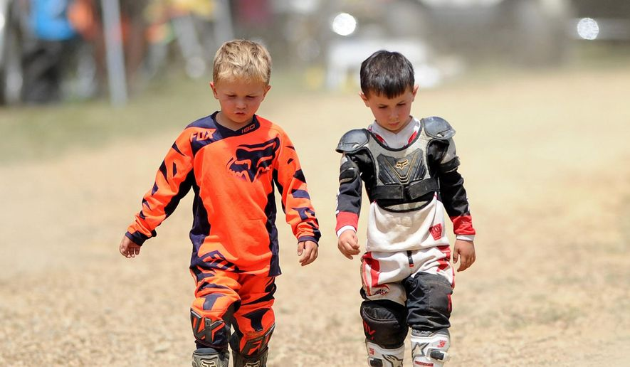 In this July 2, 2016 photo, Keegan McDade, right, walks with his friend Everett Rogan at the first annual Bikes, Bands and BBQ before competing in the PAMX Mini Motocross race at the High Voltage MX Park in Ford City, Pa. Keegan, who was diagnosed with acute lymphoblastic leukemia, rides while undergoing chemotherapy treatments. His family has established Keegan's Krew to raise money for research to support other children diagnosed with leukemia. (Pam Panchak /Pittsburgh Post-Gazette via AP)