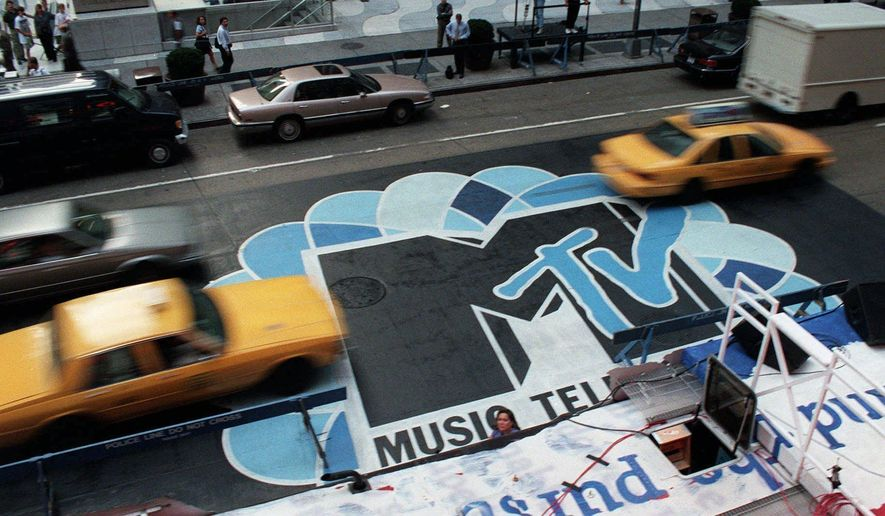 FILE -- In this Sept. 3, 1996, file photo, traffic moves along 6th Avenue in New York, over the logo painted in the street outside Radio City Music Hall for the MTV Music Video Awards ceremony. MTV announced July 28, 2016, that it is rebranding VH1 Classic as MTV Classic and the channel will focus on 1990s and early 2000s nostalgia. (AP Photo/Todd Plitt, File)