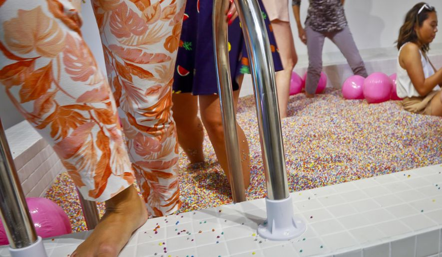 Visitors walk into a large pool filled with faux confetti-colored sprinkles, the biggest attraction of ice cream-themed works of art previewed at the Museum of Ice Cream, Thursday July 28, 2016, in New York. The museum opens on Friday and runs through Aug. 31. (AP Photo/Bebeto Matthews)