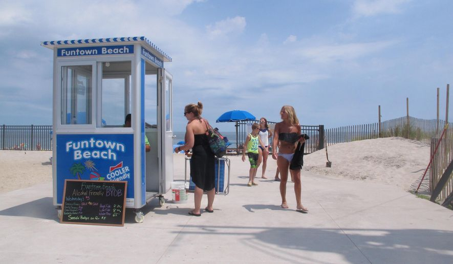 This July 27, 2016 photo shows patrons at the entrance to a private beach where the Funtown Pier once stood in Seaside Park, N.J. The pier's owner says new height restrictions imposed this week by the town will prevent him from rebuilding the historic pier, and prompt him to seek other uses for the land, possibly including a beach club. (AP Photo/Wayne Parry)