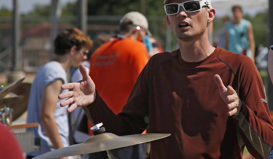 Kevin McDonald, Edmond Memorial High School English teacher, directs the percussion session of the band during a practice in Edmond, Okla., Thursday, July 28, 2016. With just three months remaining before voters head to the polls to consider a one-cent sales tax increase to boost funding for public education, Gov. Mary Fallin has suggested a special session to consider an alternative proposal. McDonald says he thinks the proposal will distract from the state question in November. (AP Photo/Sue Ogrocki)