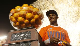 FILE - In this Dec. 31, 2015, file photo, Clemson quarterback Deshaun Watson (4) poses with the Orange Bowl trophy following an NCAA college football semifinal playoff game against Oklahoma, in Miami Gardens, Fla. The College Football Playoff has abandoned a plan to play its semifinals on most New Year's Eves after television ratings tumbled last year, moving the dates of future games to ensure they will be played either on a Saturday or a holiday.The changes will start with the 2018 season.  (AP Photo/Joe Skipper, File)