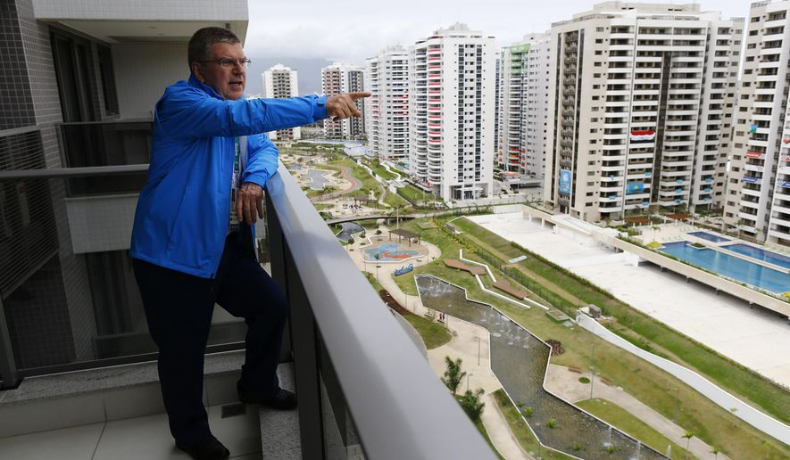 Tomas Bach, President of the International Olympic Committee, looks out from his balcony after moving into his room in the Olympic village in Rio de Janeiro, Brazil, July 28, 2016. (Ivan Alvarado/Pool Photo via AP)