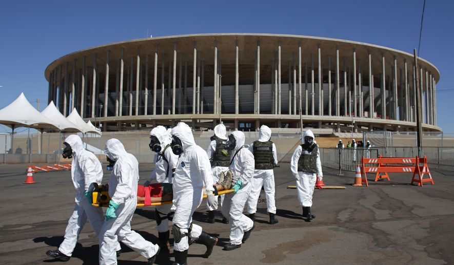Soldiers take part in an exercise drill, simulating their reaction to a chemical attack outside the National Stadium, which will host 2016 Summer Olympics soccer matches in Brasilia, Brazil, Thursday, July 28, 2016. Double the number of military and police are expected to patrol during the games, compared to London in 2012, and while most will be concentrated at sporting venues, tourist landmarks will also be heavily patrolled. (AP Photo/Eraldo Peres)