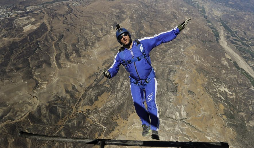 In this Monday, July 25, 2016 photo, skydiver Luke Aikins jumps from a helicopter during his training in Simi Valley, Calif. After months of training, this elite skydiver says he's ready to leave his chute in the plane when he bails out 25,000 feet above Simi Valley on Saturday. That's right, no parachute, no wingsuit and no fellow skydiver with an extra one to hand him in mid-air. (AP Photo/Jae C. Hong)
