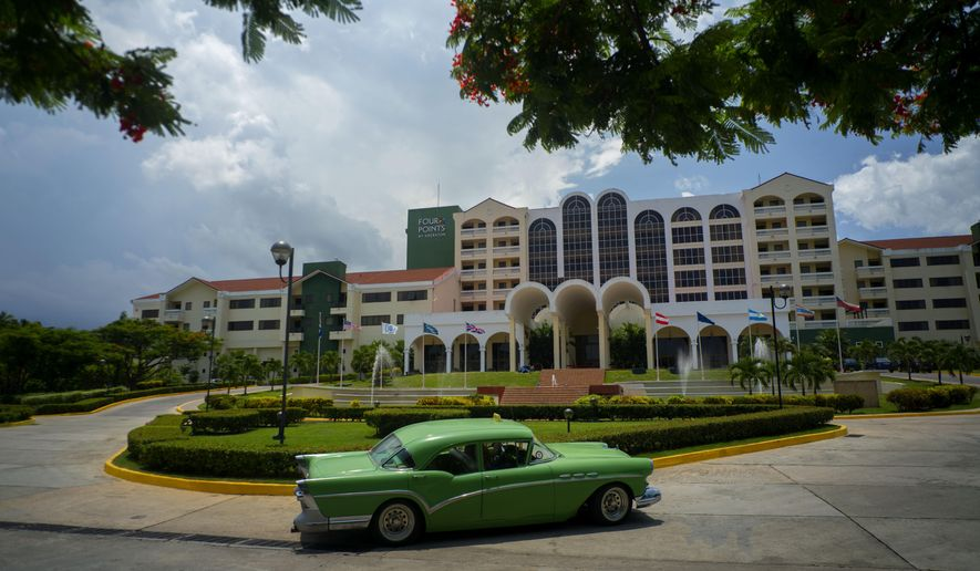 In this June 28, 2016 photo, a vintage car passes in front of the Four Points by Sheraton hotel in Havana, Cuba. American hotel giant Starwood has begun managing this hotel run by the Cuban military, opening one of the biggest holes in the U.S. trade embargo on Cuba since Presidents Barack Obama and Raul Castro declared detente in Dec. 2014. (AP Photo/Ramon Espinosa)