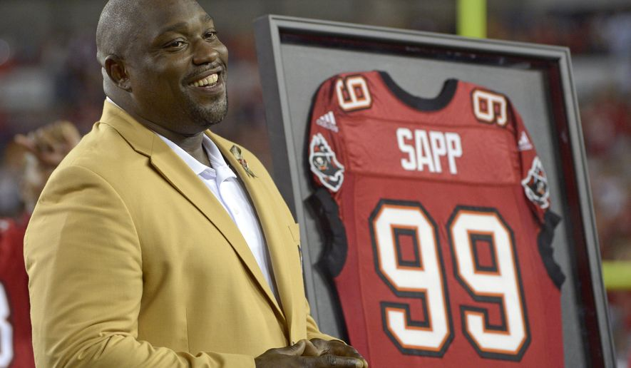 FILE - In this Nov. 11, 2013, file photo, former Tampa Bay Buccaneers player Warren Sapp smiles after being inducted in the Ring of Honor ceremony during halftime in an NFL football game between the Tampa Bay Buccaneers and the Miami Dolphins in Tampa, Fla. Sapp was bitten by a shark during a fishing trip off the Florida Keys on Wednesday, July 27, 2016. (AP Photo/Phelan M. Ebenhack, File)
