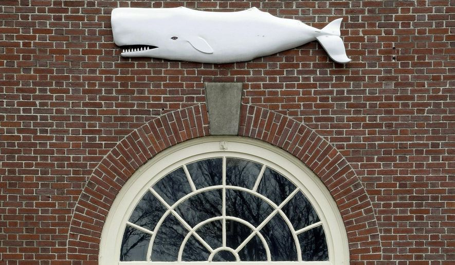 FILE - In this Tuesday, Dec. 8, 2015 file photo the likeness of a whale adorns a door at the New Bedford Whaling Museum in New Bedford, Mass. The museum has compiled a digital archive of more than a hundred thousand names of men who embarked on whaling voyages out of the Massachusetts port before the final one in 1927. (AP Photo/Stephan Savoia, File)