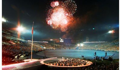 This photo combo shows a July 19, 1996 file photo of the 1996 Summer Olympic Games opening ceremony at Centennial Olympic Stadium, top, and a Friday July 15, 2016 photo of fireworks after an Atlanta Braves baseball game at what is now named Turner Field in Atlanta. The 85,000-seat main stadium was the site of athletics and both the opening and closing ceremonies. Afterward, the arena was converted into a 50,000-seat baseball park and renamed after the Braves' owner, Ted Turner. The Braves have fallen on hard times and are moving to SunTrust Park in 2017. Georgia State is exploring the possibility of another conversion, which would downsize Turner Field into a 30,000-seat football stadium. (AP Photo/Ed Reinke, File, John Bazemore)